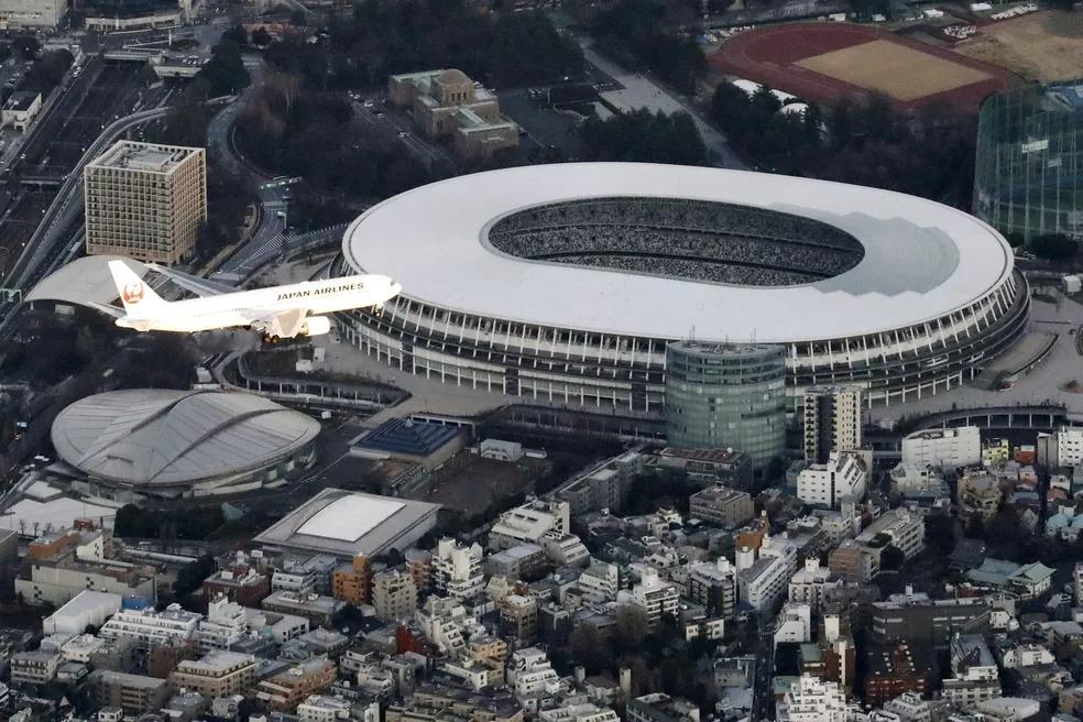 Avião sobrevoa o Estádio Nacional de Tóquio — Foto: Kyodo/via REUTERS