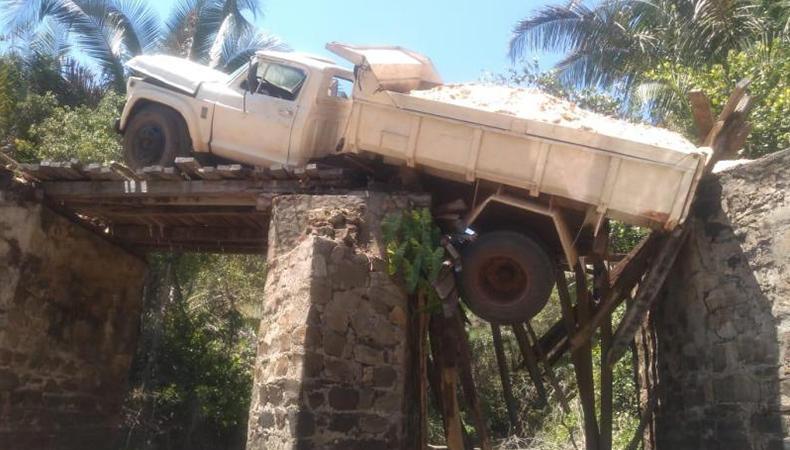 """Ponte rompe estrutura e caminhão caçamba fica """"pendurado"""" (Reprodução/ Jornal de Ilha Grande)"""