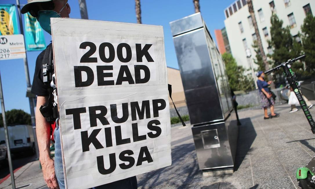 """""""200 mil mortos. Trump mata os EUA"""", diz a placa de um manifestante Foto: Mario Tama / AFP"""
