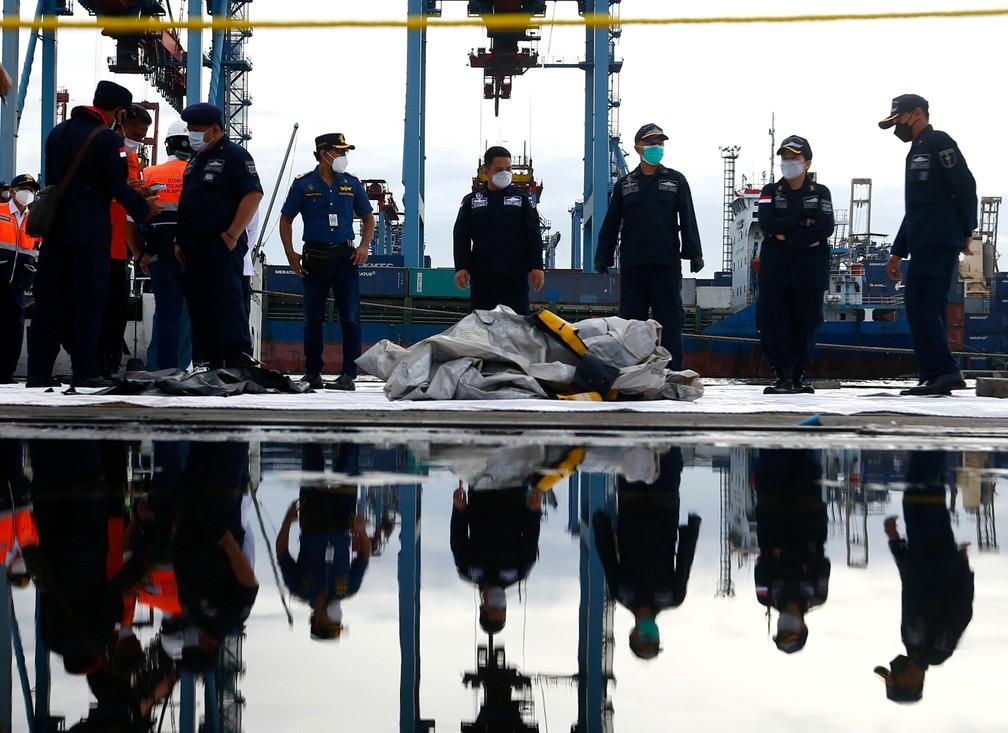 Equipe de resgate organiza sacos que contêm partes de corpos recuperados no local da queda deo avião (Foto: Aji/AFP)