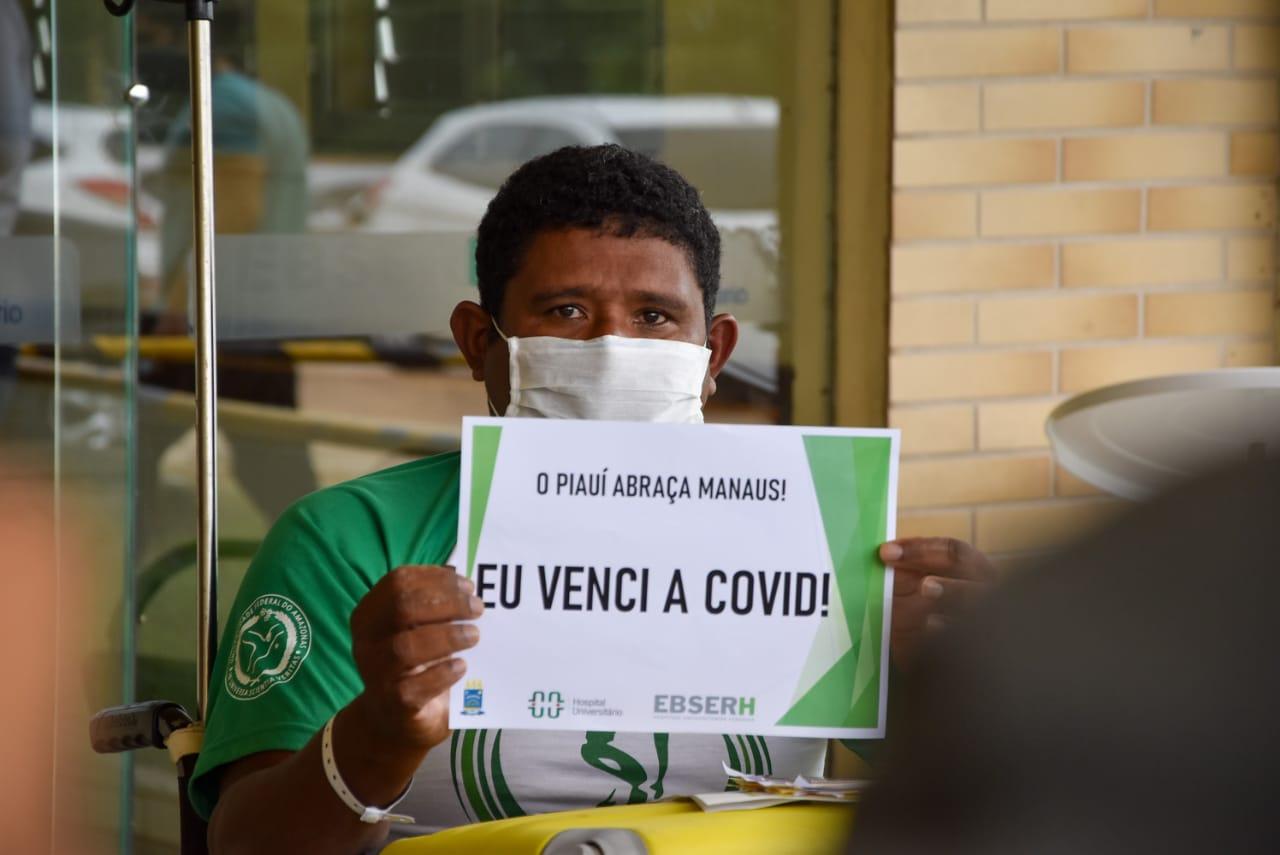 """Venezuelano Leonardo segura placa """"""""eu venci a covid-19"""""""" (Foto: Romário Farias SCS/UFPI)"""