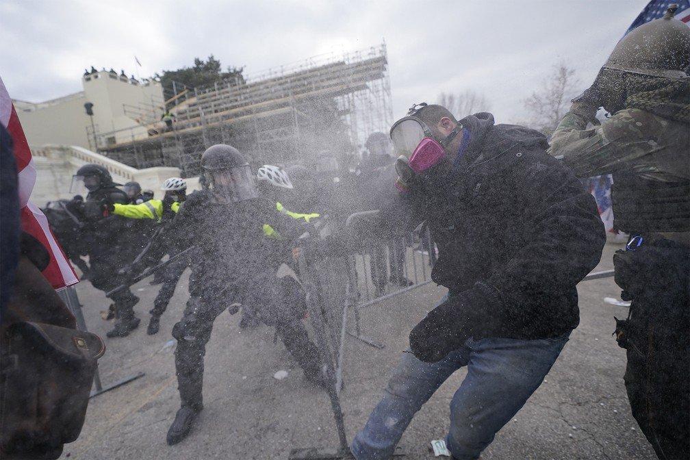Confronto entre policiais e invasores do Capitólio (Foto: Julio Cortez/AP)
