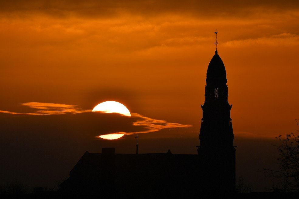 Sol se põe por trás de igreja na França - Foto: AFP