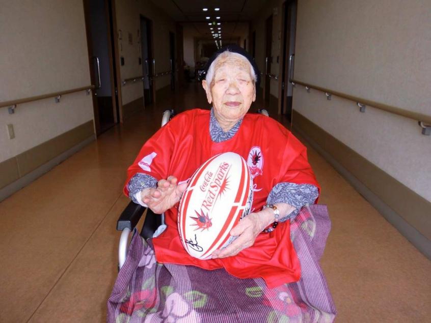 Kane Tanaka com o uniforme do time de rugby Coca-Cola Red Sparks, clube da região da anciã (Reprodução/Twitter Kane Tanaka)