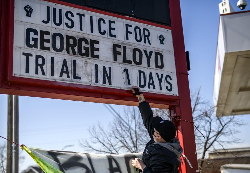 O ativista Billy Briggs ajusta o painel que pede justiça para George Floyd no julgamento do policial Derek Chauvin — Foto: Stephen Maturen/Getty Images via AFP