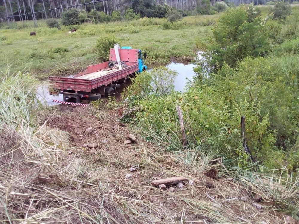 Caminhão teria quebrado a barra de direção e caído no córrego (Foto: Canal 121)