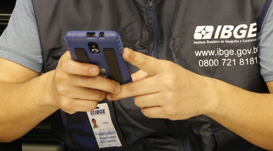 #PraCegoVer A foto mostra duas mãos segurando um dispositivo móvel de coleta, utilizado nas pesquisas do IBGE