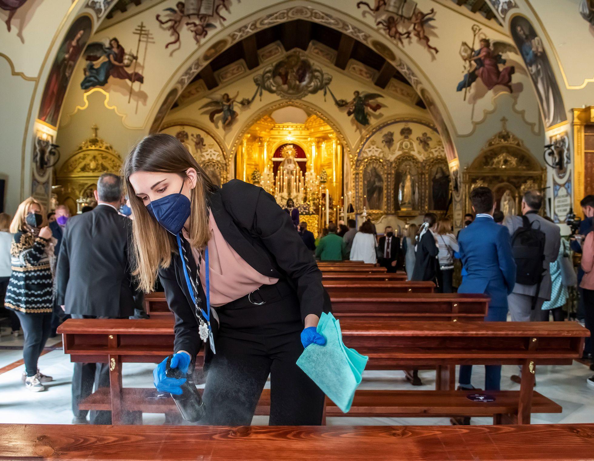 Jovem desinfeta os bancos da igreja de Santa Genoveva, em Sevilha - RAÚL CARO / EFE