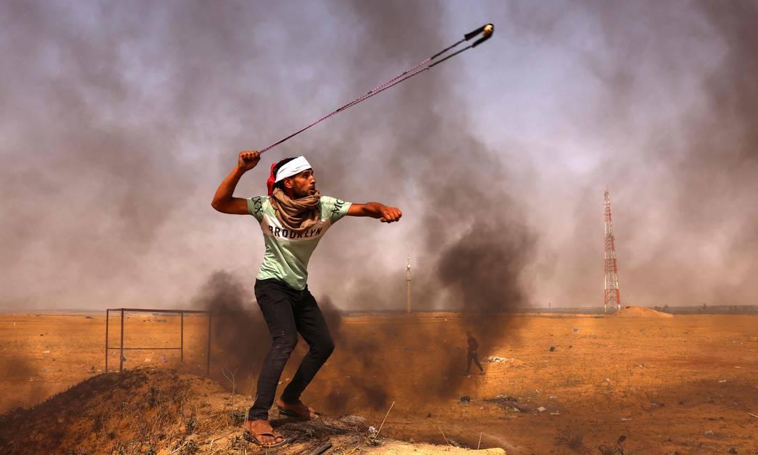Manifestante palestino atira pedras com um estilingue próximo a pneus em chamas durante um protesto na fronteira com Israel, a leste de Rafah, no sul da Faixa de Gaza Foto: SAID KHATIB / AFP