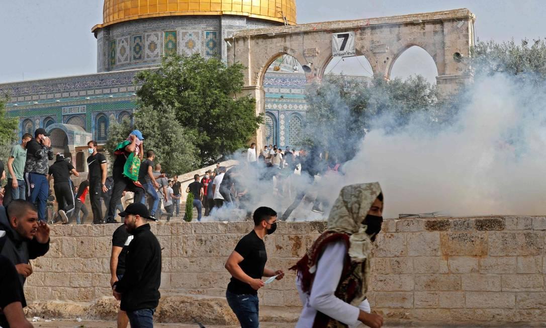 Palestinos correm para buscar proteção do gás lacrimogêneo lançado pelas forças de segurança israelenses durante o Dia de Jerusalém Foto: AHMAD GHARABLI / AFP