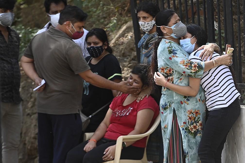 Parentes lamentam a morte de familiar com Covid-19 do lado de fora de um necrotério em Nova Délhi, capital da Índia, nesta segunda (24) — Foto: Money Sharma/AFP