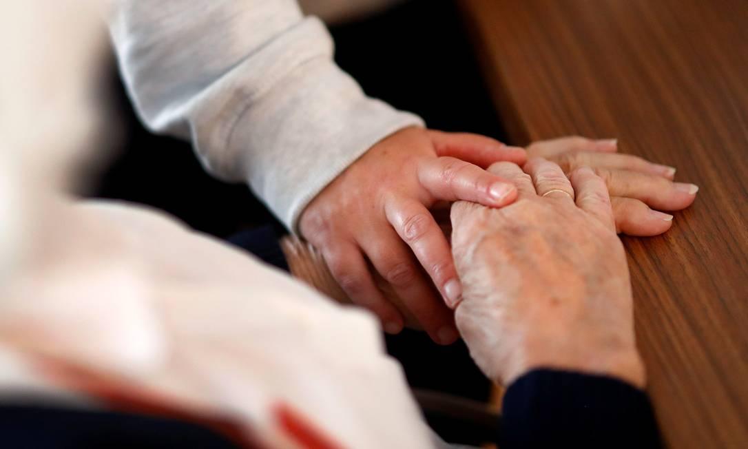 """Cuidador segura a mão de um residente da """"residência de idosos Emilia"""" em Darmstadt, Alemanha Foto: KAI PFAFFENBACH / REUTERS"""