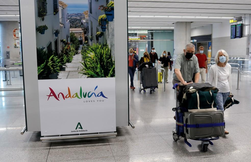 Turistas de máscaras chergam no aeroporto em Málaga, na Espanha