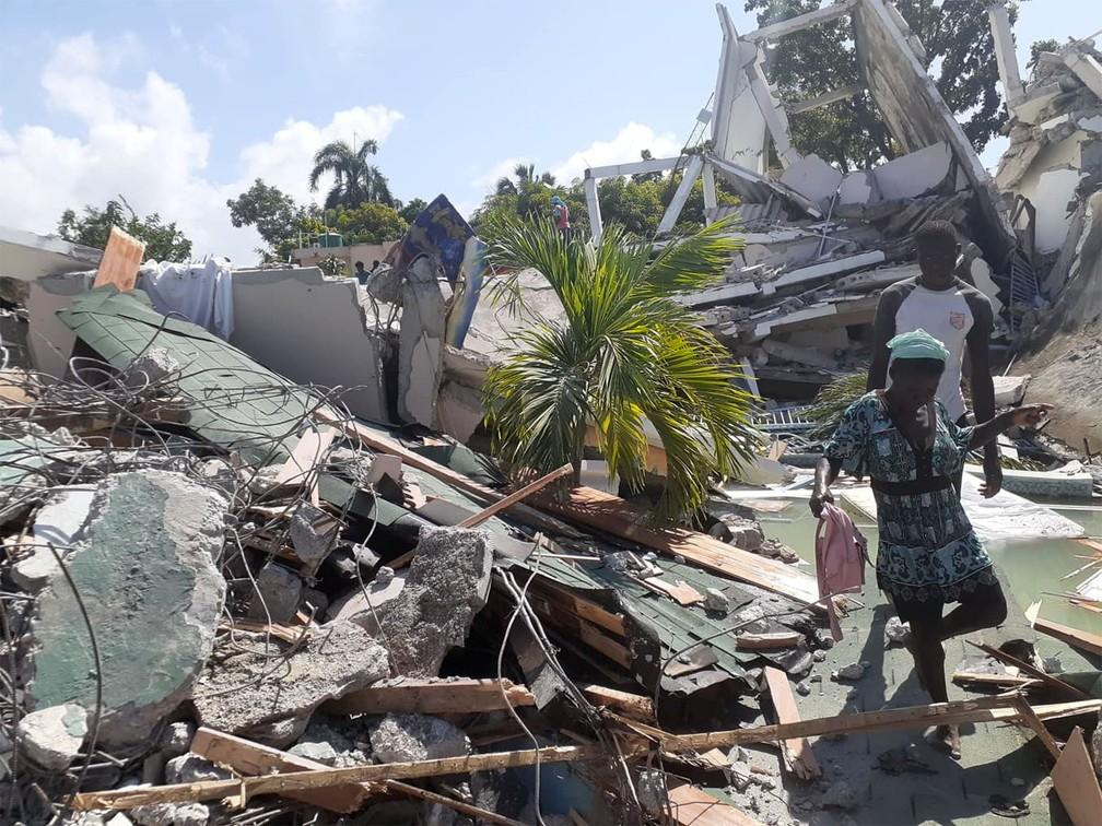 Pessoas caminham entre escombros após terremoto no Haiti