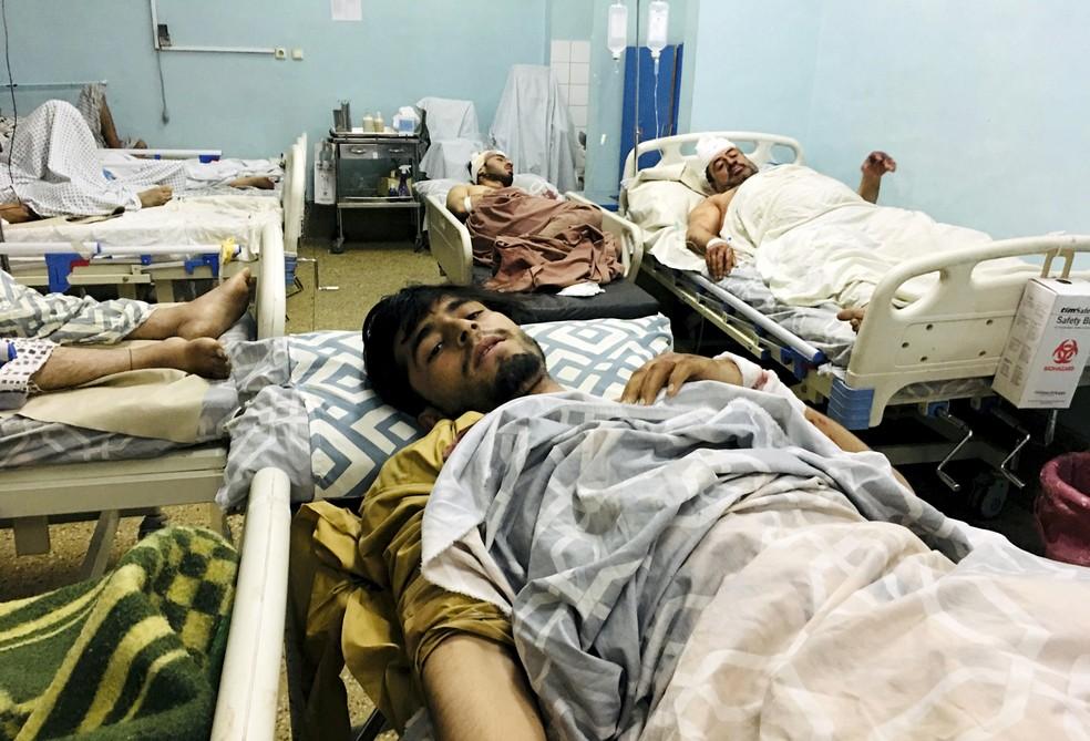 Afegãos feridos internados em hospital de Cabul após o atentado terrorista no aeroporto de Cabul, no Afeganistão, em 26 de agosto. Dois homens-bomba e homens armados atacaram afegãos que se aglomeravam no portão Abadia e soldados americanos que faziam a triagem para os voos de retirada do país. — Foto: Mohammad Asif Khan/AP