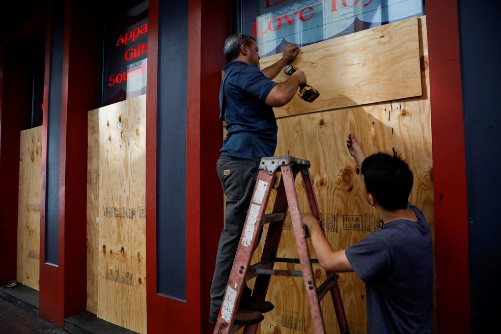 Homens colocam madeira compensada em frente a uma loja em preparação para o furacão Ida, em Nova Orleans — Foto: Marco Bello/Reuters