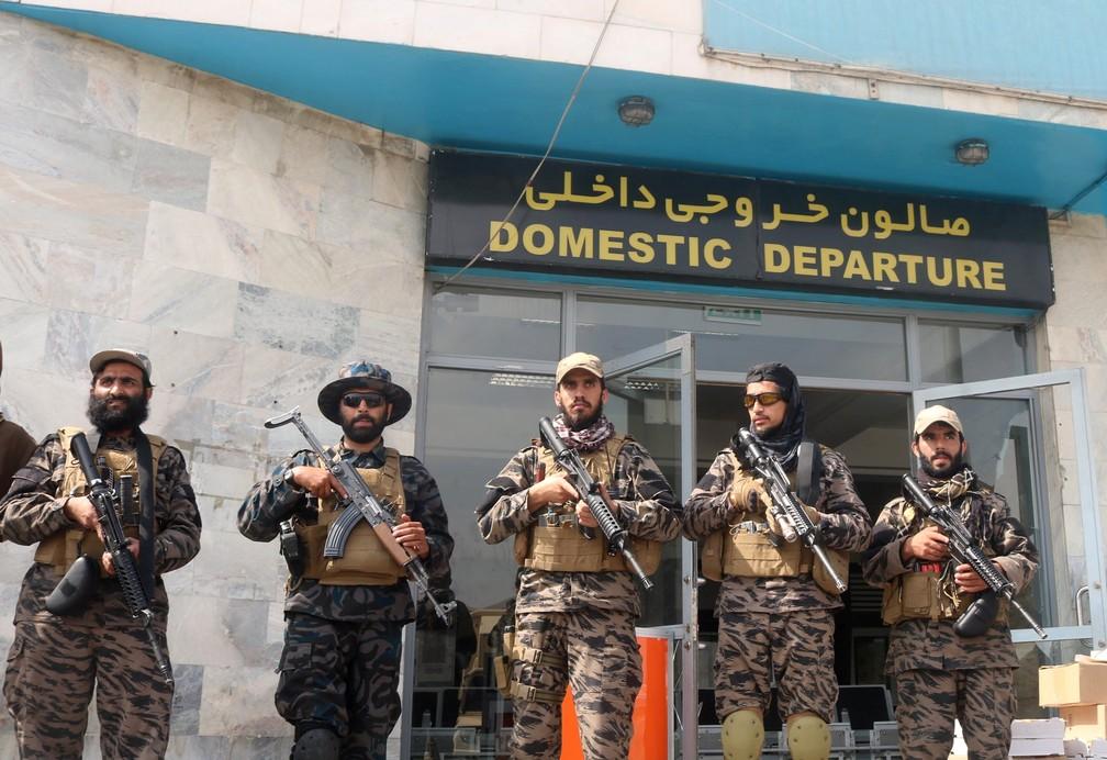 Combatentes do talibã fazem a guarda na porta de aeroporto
