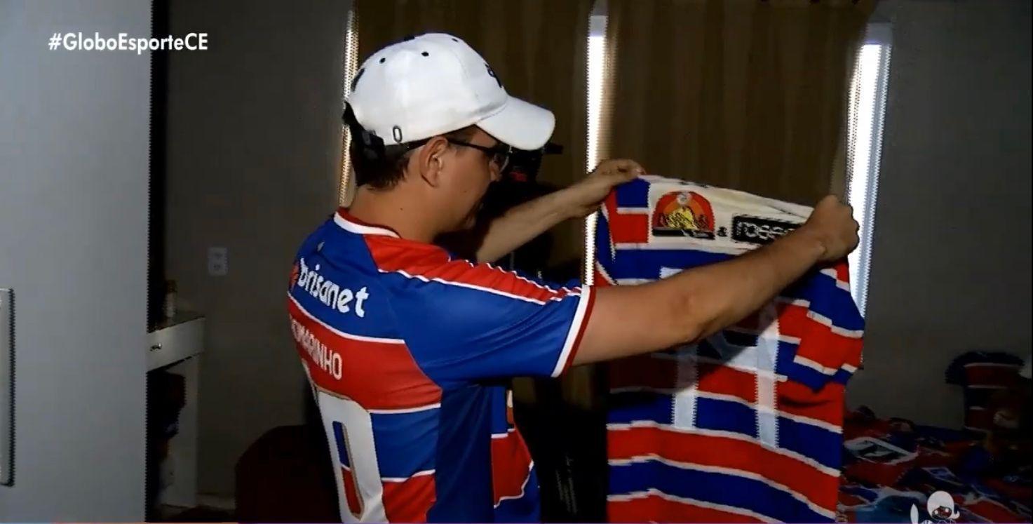 Torcedor mostra com orgulho uma camisa de sua coleção. (Foto: Reprodução - TV Verdes Mares)