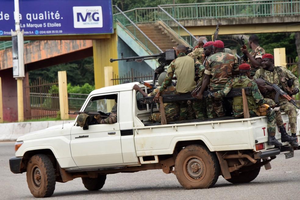 Militares de Guiné em caçamba de caminhonete passam pelo centro de Conakry — Foto: CELLOU BINANI / AFP
