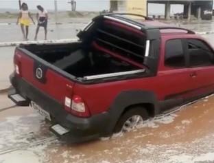 Com solo encharcado, asfalto cede e carros atolam na praia de Atalaia